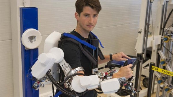 André Schiele, leading ESA's telerobotics lab, demonstrating remote robotic operations. Donning an exoskeleton that weighs just 10 kg, an operator can control a robot - commands and feedback are sent over the regular cell-phone network. Copyright: ESA