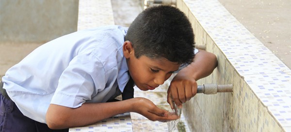 A child is sipping water from an open tap in Nagpur, India. Photo: IC-Impacts.