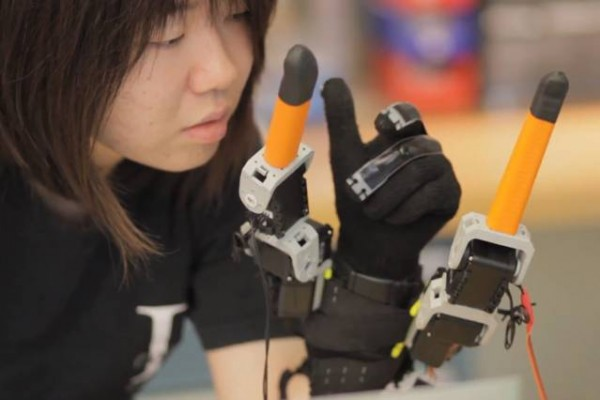 "Faye Wu, a graduate student in mechanical engineering, demonstrates the ""supernumerary robotic fingers"" device. Photo: Melanie Gonick"