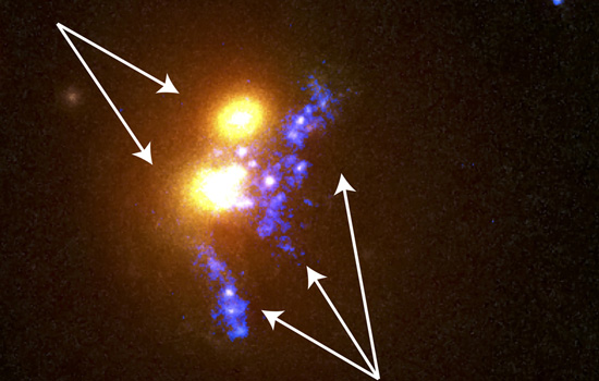 """A zoom-in shows the two merging central cluster galaxies in yellow/orange and the """"beads-on-a-string"""" star formation in bright blue. Credit: NASA, ESA and RIT"""