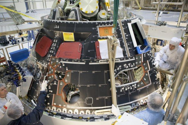 Inside the Operations and Checkout Building high bay at NASA's Kennedy Space Center in Florida, technicians dressed in clean-room suits install a back shell tile panel onto the Orion crew module. Image Credit: NASA/Dimitri Gerondidakis