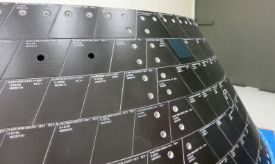Two one-inch-wide holes have been drilled into tiles on Orion's back shell to simulate micrometeoroid orbital debris damage . Sensors on the vehicle will record how high temperatures climb inside the hole during Orion's return through Earth's atmosphere following its first flight in December. Image Credit: NASA