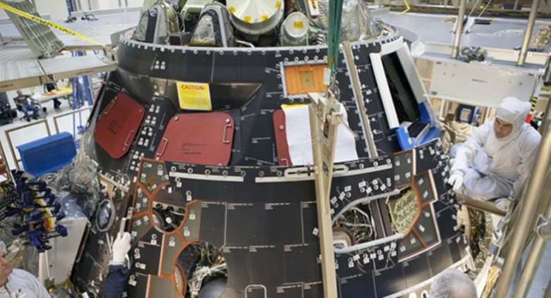 Technicians install a protective shell onto the Orion crew module for its first test flight this December.