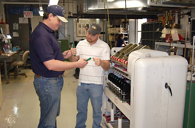 In the textile mill at the Southern Regional Research Center, materials engineer Chris Delhom (left) and technician E.J. Deshotel examine yarn packages in front of the miniature spinning equipment. Photo by Melissa Dunn.