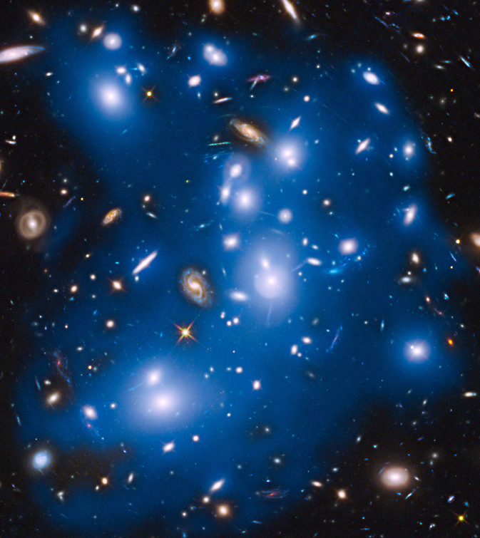 Massive galaxy cluster Abell 2744, nicknamed Pandora's Cluster, takes on a ghostly look where total starlight has been artificially colored blue in this Hubble view. Image Credit: NASA/ESA/IAC/HFF Team, STScI