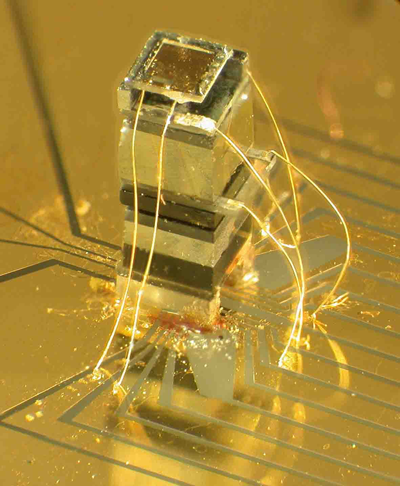 The NIST chip-scale magnetometer. The sensor is about as tall as a grain of rice. The widest block near the top of the device is an enclosed, transparent cell that holds a vapor of rubidium atoms.