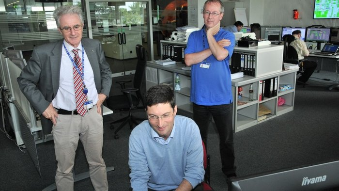 Rosetta Spacecraft Operations Manager Sylvain Lodiot, sitting, monitoring a thruster burn on 21 May 2014 in the mission's Dedicated Control Room. ESA's Head of Mission Operations, Paolo Ferri, stands at left, while Mission Manager Fred Jansen looks on, at right. Copyright ESA