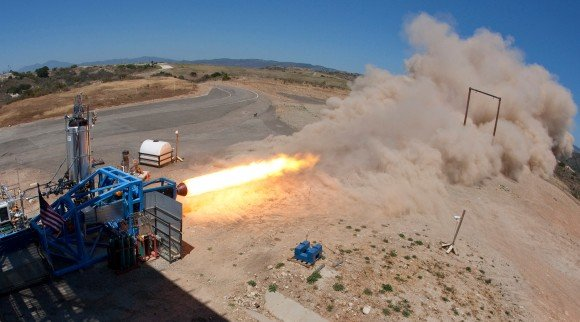 A SpaceShipTwo solid rocket motor is tested on a stand in the Mojave desert. Recent delays led Scaled Composites to swtich from a rubber-based fuel to one chemically similar to nylon. (Photo Credit: Virgin Galactic)