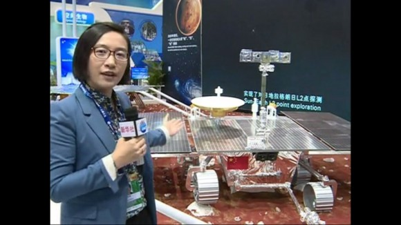 China View reporter Lai Yuchen is seen describing and pointing out the future Sino-Mars rover with plans for a 2020 launch coinciding with the NASA/JPL Mars 2020 rover mission . (Click still image for video Link) (Photo/Video Credit: China View)