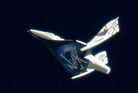 SpaceShipTwo is shown in the feathered configuration in an earlier unpowered test flight. While the test pilots tested the feathering in the lower, denser atmosphere, the vehicles was flying much slower and stresses on the vehicle remained within safety margins. (Photo Credit: Virgin Galactic)