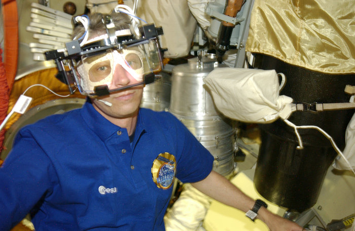 ESA astronaut Thomas Reiter wearing ESA's Eye Tracking Device during his six-month Astrolab mission to the International Space Station in 2006.  How do astronauts in space cope when the inner ear can no longer rely on gravity? How well do astronauts focus on a computer screen when floating by, and how do they judge speed? To investigate these questions, a team led by Professor Andrew Clarke based in Berlin, Germany, designed a series of experiments to measure astronauts' eye movements as they worked on the International Space Station. Researchers needed a robust method to track the eyes without interfering with the astronaut's normal work. The answer came in the form of a helmet feeding high-performance image-processing chips similar to those found in consumer cameras. Copyright ESA/NASA
