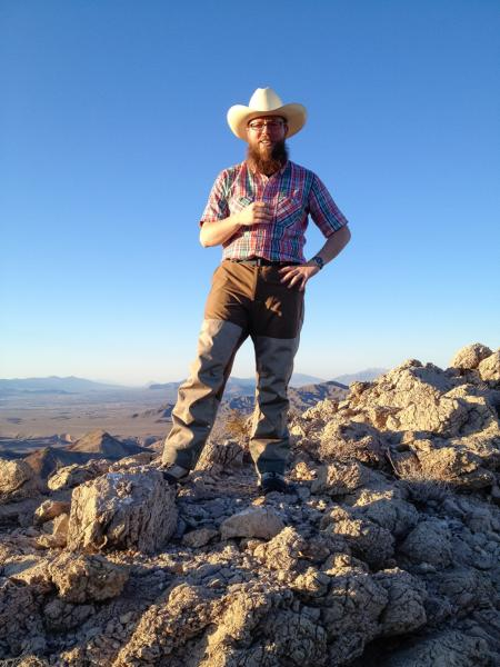 Caltech Professor of Geobiology Woody Fischer atop a mountain of Precambrian carbonates in the southern Nopah Range in Death Valley, California. Microbes are probably responsible for some portion of this deposit, which is approximately 630 million years old. Credit: Courtesy Woody Fischer/Caltech