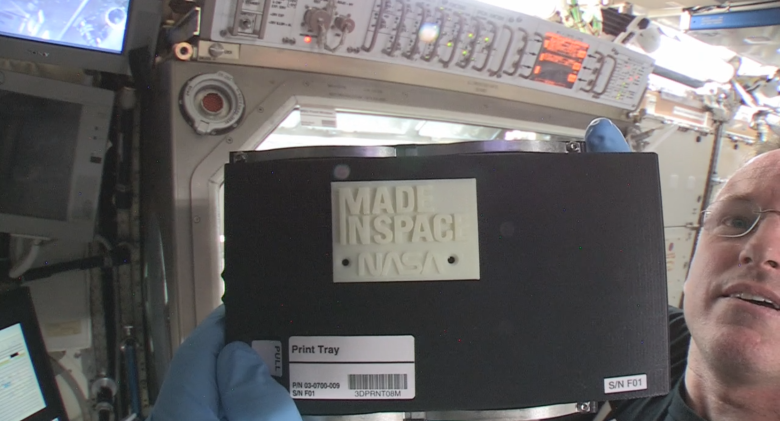 "International Space Station Commander Barry ""Butch"" Wilmore holds up the first object made in space with additive manufacturing or 3-D printing. Wilmore installed the printer on Nov. 17, 2014, and helped crews on the ground with the first print on Nov. 25, 2014. Image Credit: NASA"