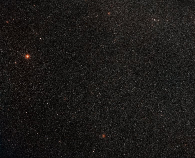 This wide-field view shows the sky around the galaxy ESO 137-001, which appears near the bottom-right of this picture. This part of the sky is in the southern Milky Way and huge numbers of stars are visible in the foreground. This picture was created from images forming part of the Digitized Sky Survey 2. Credit: ESO/Digitized Sky Survey 2