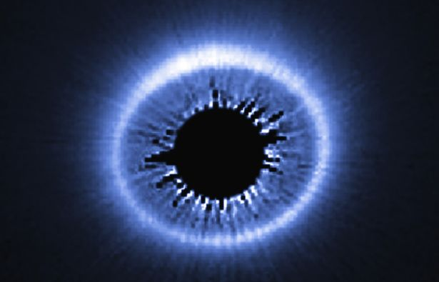 Located 169 light-years from Earth, circumstellar disk HD 181327 is seen nearly face-on. The image, taken with the Hubble Space Telescope, reveals a vast disk of dust and debris around the central star, whose light has been blocked out so that the very faint reflected light from the dust structures can be seen. For scale, the blocked-out hole in the center is almost as wide as our solar system.