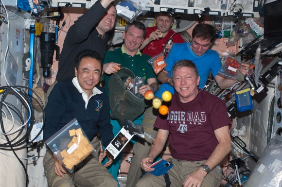 The Expedition 28 crew on the International Space Station celebrates after a fresh food delivery in 2011. Credit: NASA