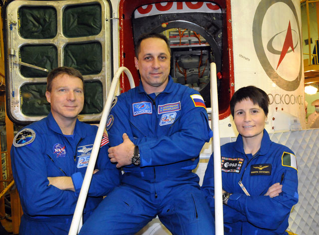 In the Integration Facility at the Baikonur Cosmodrome in Kazakhstan, Expedition 42/43 crewmembers Terry Virts of NASA (left), Anton Shkaplerov of the Russian Federal Space Agency (Roscosmos, center) and Samantha Cristoforetti of the European Space Agency (right) pose for pictures Nov. 19 in front of their Soyuz TMA-15M spacecraft. Credit: NASA/Viktor Ivanov.