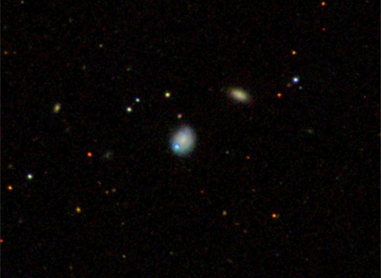 The dwarf galaxy Markarian 177 (center) and its unusual source SDSS1133 (blue) lie 90 million light-years away. The galaxies are located in the bowl of the Big Dipper, a well-known star pattern in the constellation Ursa Major. Image Credit: Sloan Digital Sky Survey