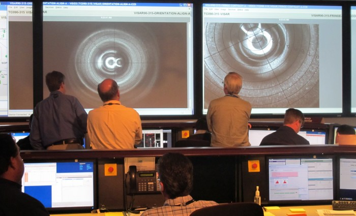 Physicists Dave Farley (left) and Peter Celliers and scientist Curtis Walter watch a live VISAR image as they monitor the deuterium fill of a keyhole capsule in the NIF Control Room during shock-timing experiments.