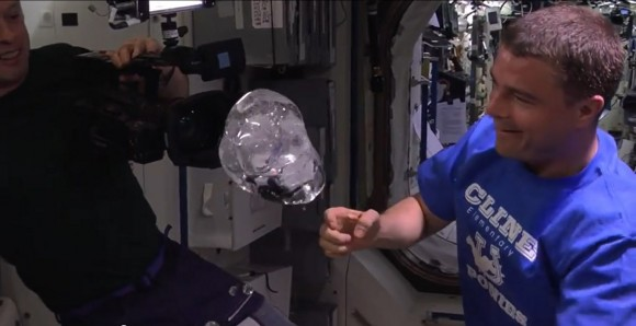 Expedition 40 commander Steve Swanson (left) and Reid Wiseman view a water bubble surrounding a video camera on the International Space Station in summer 2014. Credit: NASA/YouTube (screenshot)