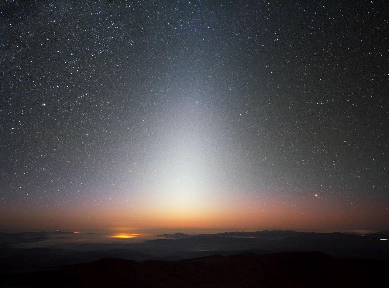 "This image beautifully captures the zodiacal light, a triangular glow seen best in night skies free of overpowering moonlight and light pollution. The photograph was taken at ESO's La Silla Observatory in Chile in September 2009, facing west some minutes after the Sun had set. A sea of clouds has settled in the valley below La Silla, which sits at an altitude of 2400 metres, with lesser peaks and ridges poking through the mist. The zodiacal light is sunlight reflected by dust particles between the Sun and Earth, and is best seen close to sunrise or sunset. As its name implies, this celestial glow appears in the ring of constellations known as the zodiac. These are found along the ecliptic, which is the eastward apparent ""path"" that the Sun traces across Earth's sky. Credit: ESO/Y. Beletsky"