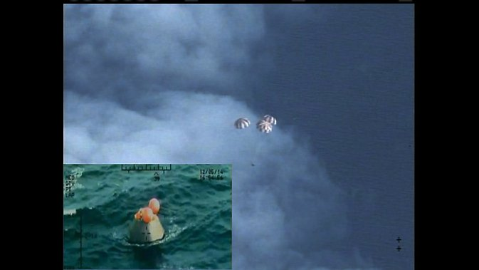 Following a perfect launch and more than four hours in Earth's orbit, NASA's Orion spacecraft is seen from an unpiloted aircraft descending under three massive red and white main parachutes and then shortly after its bullseye splashdown in the Pacific Ocean, 600 miles southwest of San Diego. During the uncrewed test, Orion traveled twice through the Van Allen belt, where it experienced periods of intense radiation, and reached an altitude of 3,600 miles above Earth. The spacecraft hit speeds of 20,000 mph and weathered temperatures approaching 4,000 degrees Fahrenheit as it entered Earth's atmosphere. Image Credit: NASA