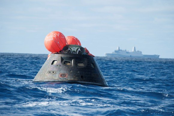 The Orion spacecraft floats in the Pacific Ocean after an uncrewed orbital flight test Dec. 5, 2014. In the background is the recovery ship, the USS Anchorage. Credit: NASA