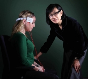 Colleen Loo demonstrates a treatment using mild electric currents. Photo: Grant Turner/Mediakoo