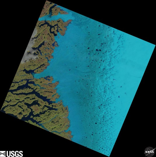 Supraglacial lakes on the Greenland ice sheet can be seen as dark blue specks in the centre and to the right of this satellite image. Credit: USGS/NASA Landsat