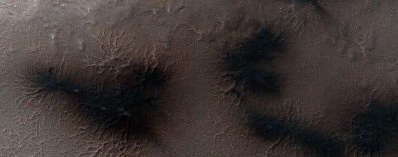 On Aug. 20, 2014, Martian dust mounds are on top of the araneiforms in 'Inca City', as well as dark areas on the terrain showing where the ice cap in the southern hemisphere burst and sent gas and dust into the surroundings. Fans in the area are pointing in multiple directions, showing how the wind has changed. Image taken by the Mars Reconnaissance Orbiter's HiRISE camera. Credit: NASA/JPL/University of Arizona