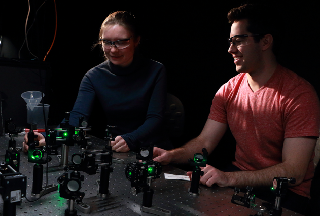 A. Jolene Mork, a fifth-year MIT graduate student in chemistry, and Mark C. Weidman, a fourth-year MIT chemical engineering graduate student, work with an array of mirrors and lenses coupled to a laser that directs a light beam to a microscope (not shown) for carrying out time-resolved photoluminescence spectroscopy experiments in the Tisdale Lab at MIT. Photo: Denis Paiste/Materials Processing Center