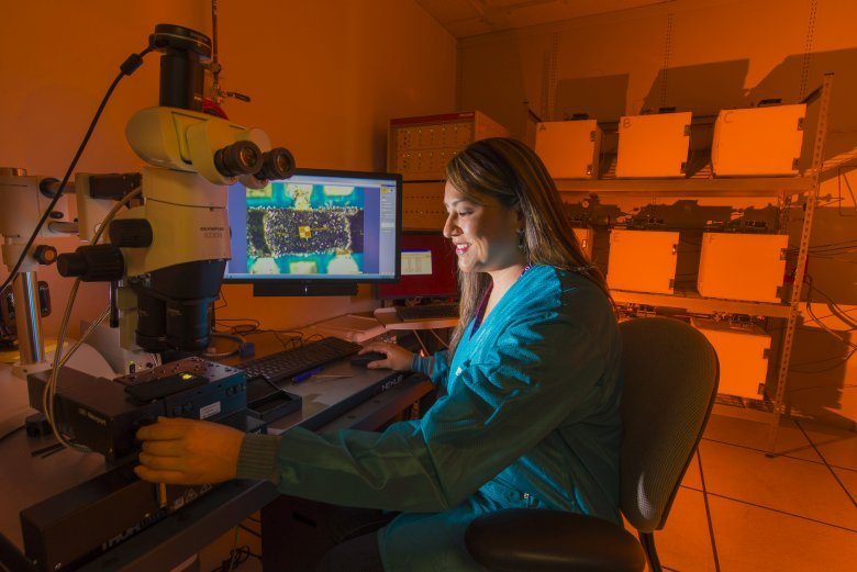 Sandia National Laboratories researcher Rachelle Thompson inspects an electronic device that's part of a 30-year Sandia program to look at how environments, including radiation from a nuclear weapon itself, could affect the performance of electronics inside a W76-1 warhead. The study begun in 2006 will provide real-time data for the first time on how electronics age within a weapon. (Photo by Randy Montoya)