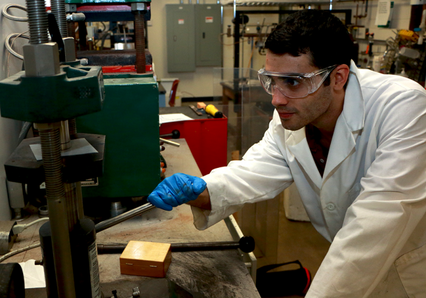MIT graduate student Zack Cordero demonstrates a uniaxial press used for consolidating loose powder into a pellet. Working under Materials Science and Engineering Department chair Christopher A. Schuh, Cordero has developed extremely hard, finely grained tungsten alloy powders and compacts. Photo: Denis Paiste/Materials Processing Center