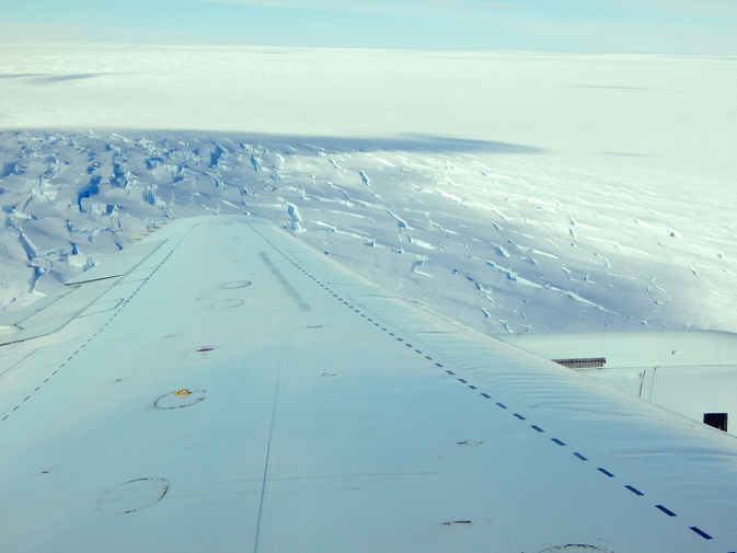 A view from an IceBridge survey flight on Nov. 3, 2014, showing a cloud's shadow on crevassed Antarctic ice. Image Credit: NASA / George Hale