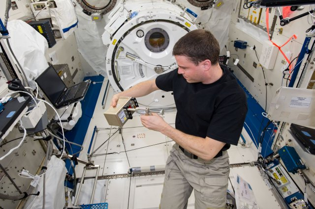 """NASA astronaut Reid Wiseman chemically """"freezes"""" a set of samples in one of the Biological Research in Canisters for the BRIC-19 investigation on the International Space Station before the sample is returned to Earth. Image Credit: NASA"""