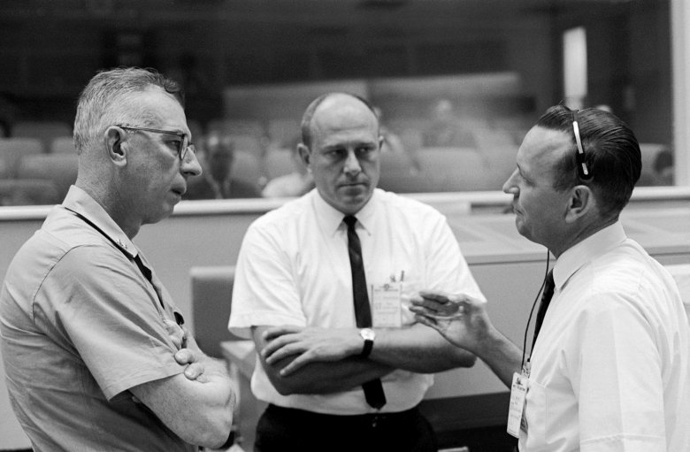 In this historical photo, former NACA staff Robert F. Thompson (center) and Christopher C. Kraft Jr. (right) brief Rear Admiral W.C. Abhau on Gemini recovery operations similar to those to be used decades later for Orion. Image Credit: NASA
