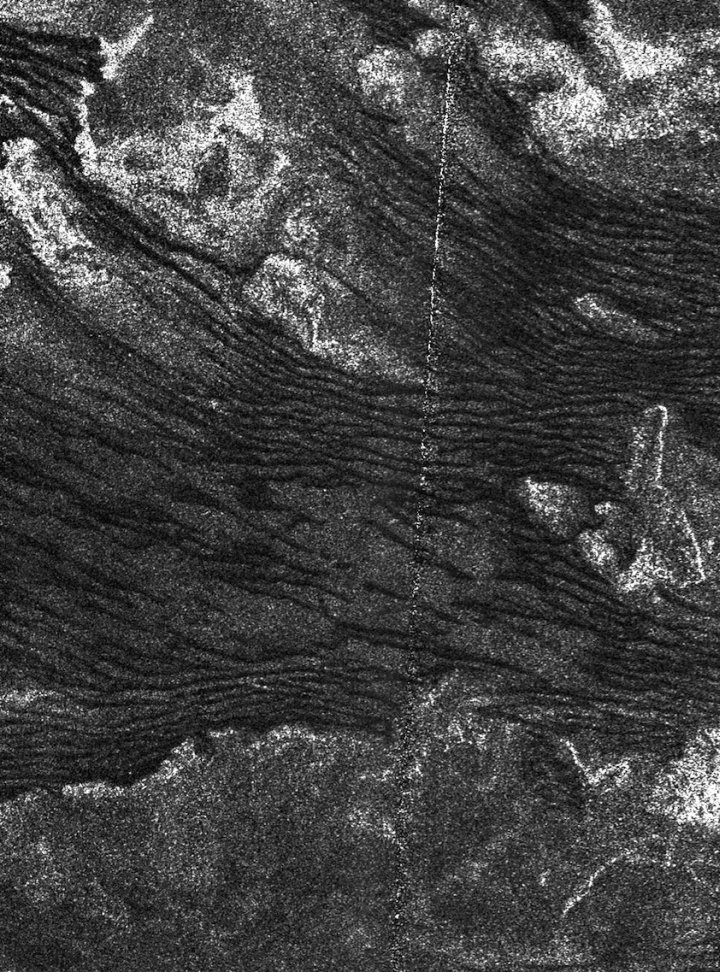 Lines of dunes crawl across the surface of Titan, Saturn's largest moon, in a radar image showing dunes as dark. Experiments at ASU's wind tunnel indicate the dune particles move only under winds that blow stronger than scientists previously thought. Photo by: NASA/JPL-Caltech/ASI