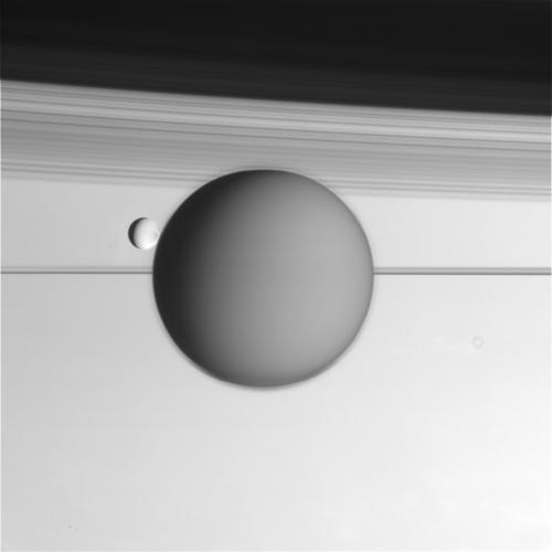 Raw Cassini image of Titan and Enceladus backdropped by Saturn's rings. Image Credit: NASA/JPL/Space Science Institute
