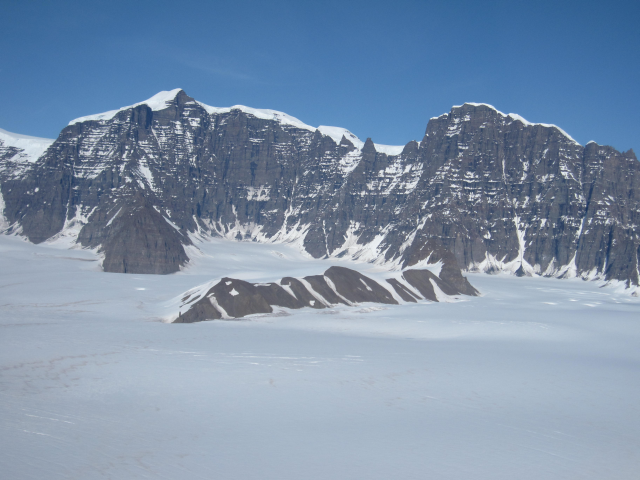 Watkins Mountains in southern East Greenland, with Greenland's highest peak, Gunbjörn Fjeld (3.7 km above sea level) in the background. The photo was taken at about 2 km above sea level, towards the 1.5 km high Watkins Escarpment cut into basalts erupted at the Paleocene-Eocene transition about 56 million years ago, much closer to sea level at that time (Photo: Peter Japsen, GEUS).