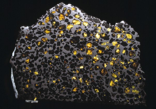 The Esquel pallasite from the Natural History Museum collections, consists of gem-quality crystals of the silicate mineral olivine embedded in a matrix of iron-nickel alloy. Credit: Copyright the Natural History Museum