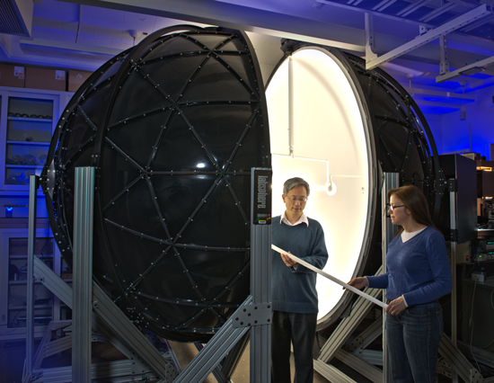 Ben Tsai (left) and Maria Nadal demonstrate one kind of solid-state light than can be mounted in the integrating sphere for measurements. Image credit: NIST