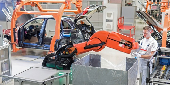 Robot picking up coolant expansion tank and giving it to his human colleague, image courtesy of audi-mediaservices.com