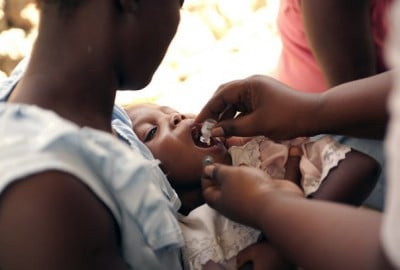 A community health worker administers cholera vaccine to a child in Haiti in 2012. Image credit: Jon Lascher/Partners In Health