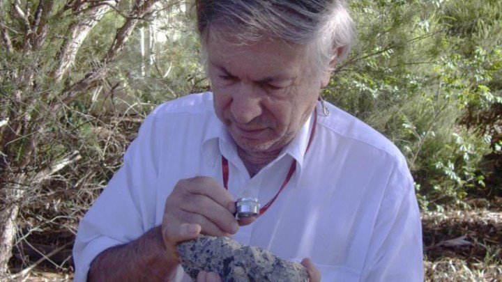 Dr Andrew Glikson with a sample of suevite - a rock with partially melted material formed during an impact.  Image: D. Seymour