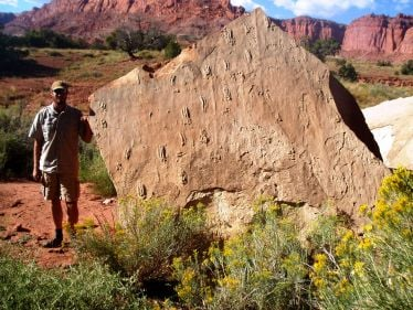 Tracy J. Thomson stands next to a block with numerous swim tracks in Capitol Reef National Park, Utah. Image credit: Tracy Thomson.