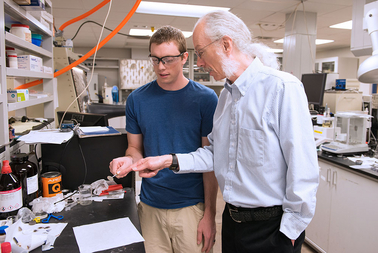Dan Buttry, professor and chair of ASU's Department of Chemistry and Biochemistry, examines a battery sample with graduate student Tylan Watkins. Photo by: Mary Zhu
