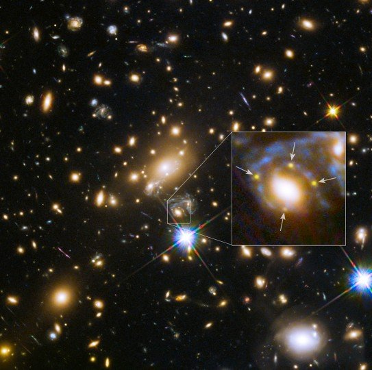 This image shows the huge galaxy cluster MACS J1149+2223, whose light took over 5 billion years to reach us. The huge mass of the cluster and one of the galaxies within it is bending the light from a supernova behind them and creating four separate images of it. The light has been magnified and distorted due to gravitational lensing and as a result the images are arranged around the elliptical galaxy in a formation known as an Einstein cross. A close-up of the Einstein cross is shown in the inset. Credit: NASA, ESA, S. Rodney (John Hopkins University, USA) and the FrontierSN team; T. Treu (University of California Los Angeles, USA), P. Kelly (University of California Berkeley, USA) and the GLASS team; J. Lotz (STScI) and the Frontier Fields team; M. Postman (STScI) and the CLASH team; and Z. Levay (STScI)