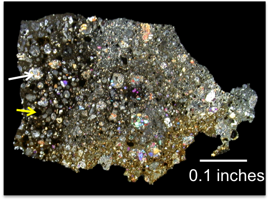 "A thin section of the meteorite from this study seen in cross-polarized light. ""Viewing it that way can help identify different minerals in the thin section – but it's also prettiest that way,"" Miller said. ""The dark section on the left is the primitive clast we've been studying. The white arrow is pointing to a large silicate chondrule, and the yellow arrow is pointing to a sulfide chondrule, which is black in this view."" (Photo courtesy of Kelly Miller)"