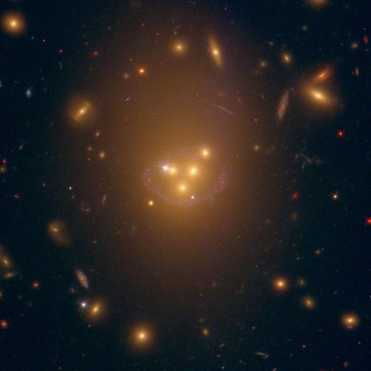 This is an approximately real-color image from the Hubble Space Telescope, of galaxy cluster Abell 3827. The galaxy cluster is made of hundreds of yellowish galaxies. At its core, four giant galaxies are smashing into each other. As the topmost of the four galaxies fell in, it left its dark matter trailing behind. The dark matter is invisible in this image, but its position is revealed by tell-tale gravitational lensing of an unrelated spiral galaxy behind the cluster, whose distorted image is seen as a blue arc. Trailing dark matter is predicted by theories in which dark matter is not perfectly dark, but feels more of the fundamental forces than just gravity. Image credit: Dr. Richard Massey (Durham University)