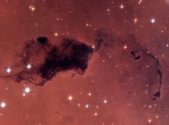 """This Hubble image features dark knots of gas and dust known as """"Bok globules,"""" which are dense pockets in larger molecular clouds. Similar islands of material in the early universe could have held as much water vapor as we find in our galaxy today, despite containing a thousand times less oxygen. Image credit: NASA, ESA, and The Hubble Heritage Team"""
